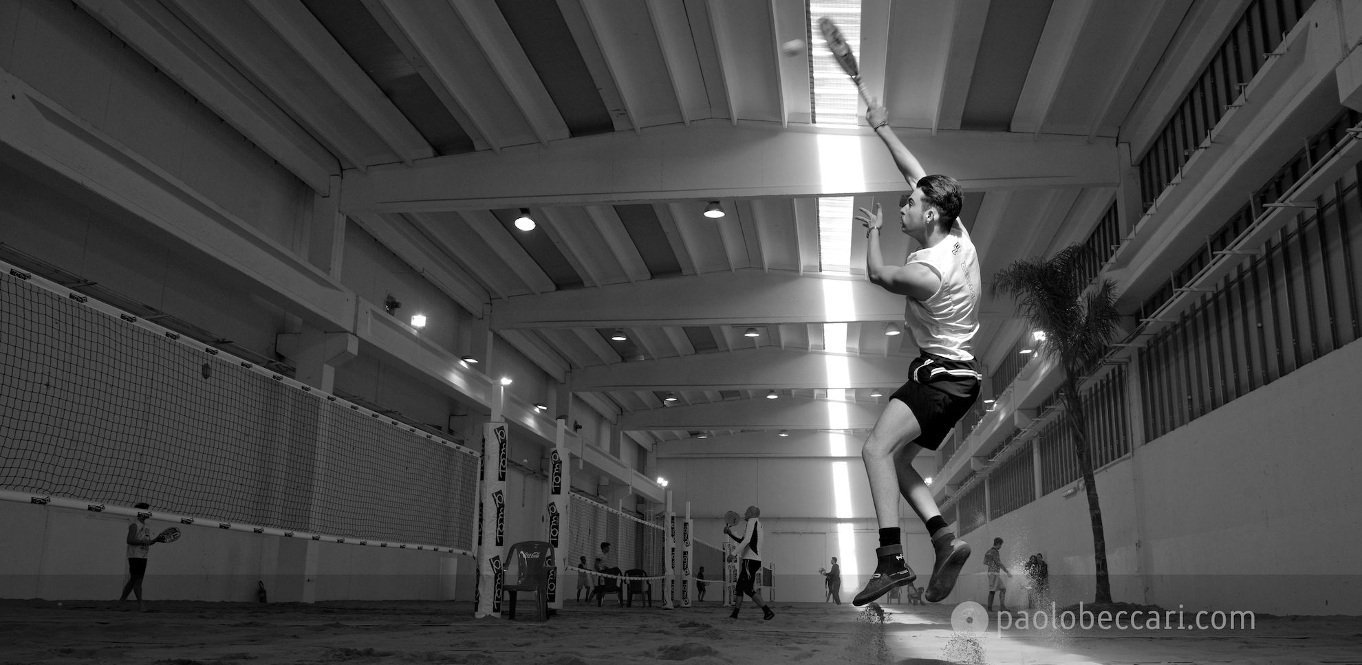 Fotografia di Beach Tennis: salto e smash in un campo indoor.